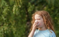 Больное чихание маленькой девочки в носовом платке на outdoors стоковые изображения rf