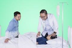 Больной мальчик расмотренный его доктором на студии стоковая фотография