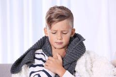 Больной мальчик страдая от кашля на софе стоковые фотографии rf
