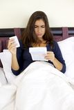 Больной молодой женщины в чтении кровати о микстуре Стоковое Фото