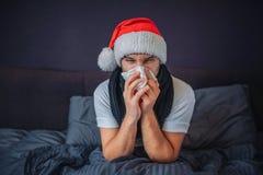 Больной молодой человек в шляпе рождества красной сидит на кровати Он покрыт с одеялом Гай чихая в ткань Он страдает Молодые стоковые фотографии rf