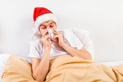 Больной молодой человек в шляпе Санта стоковые фотографии rf