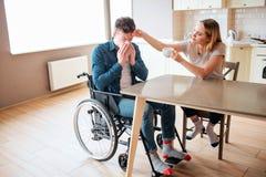 Больной молодой человек с особенными потребностями и инвалидностью чихая Больной и больной парень Молодая женщина сидит рядом с в стоковое изображение rf