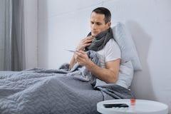 Больной мужск человек смотря термометр Стоковая Фотография