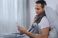Больной мужчина брюнет сидя в semi положении Стоковое Изображение