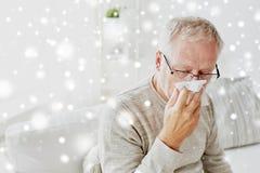 Больной старший человек при бумажный wipe дуя его нос Стоковое Фото