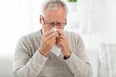Больной старший человек при бумажный wipe дуя его нос стоковые изображения