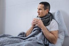 Больной человек держа чашку с горячим чаем Стоковые Изображения