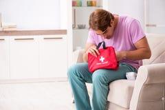 Больной человек дома с бортовой аптечкой стоковое фото
