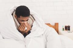 Больной человек дуя его нос в кровати дома стоковое фото rf