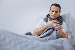 Больной человек проверяя его температуру Стоковое Фото