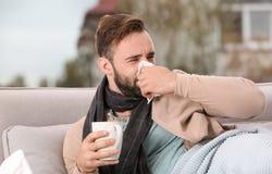 Больной человек с чашкой горячего чая для кашля на софе стоковое фото