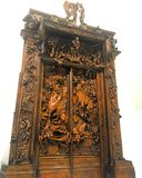 Большая, высекаенная дверь с древесиной и статуи металла Стоковая Фотография RF