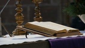 Большая книга священника лежит на алтаре в старой католической церкви акции видеоматериалы