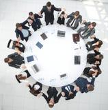 Большая команда дела сидя на круглом столе и поднимая его руки вверх Стоковая Фотография