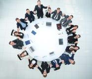 Большая команда дела сидя на круглом столе и поднимая его руки вверх Стоковое Изображение