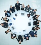 Большая команда дела сидя на круглом столе и поднимая его руки вверх Стоковые Изображения RF