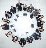 Большая команда дела сидя на круглом столе и поднимая его руки вверх Стоковое Изображение RF