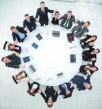 Большая команда дела сидя на круглом столе и поднимая его руки вверх Стоковые Изображения