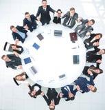 Большая команда дела сидя на круглом столе и поднимая его руки вверх Стоковая Фотография RF