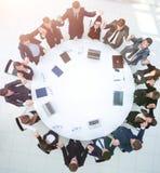 Большая команда дела сидя на круглом столе и поднимая его h Стоковое Фото