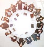 Большая команда дела сидя на круглом столе и поднимая его h Стоковая Фотография