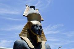 Большая красивая каменная статуя черного гордого величественного фараона в золотой крышке, кроне в форме кувшина против голубого  стоковая фотография