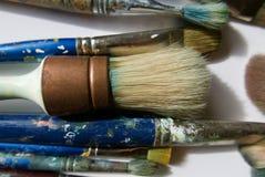 Большая, круглая щетка ` s художника с медным ferrule, в группе в составе пакостные щетки стоковое изображение