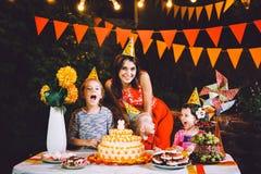 Большая мать и 3 дет на праздничной таблице с помадками и тортом в дворе украшенном с светами и гирляндой o Стоковые Фотографии RF