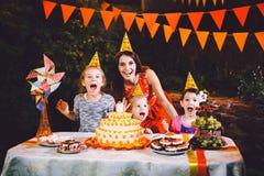 Большая мать и 3 дет на праздничной таблице с помадками и тортом в дворе украшенном с светами и гирляндой o Стоковые Фото