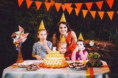 Большая мать и 3 дет на праздничной таблице с помадками и тортом в дворе украшенном с светами и гирляндой o Стоковые Изображения