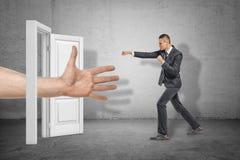 Большая мужская открытая рука появляясь через белый вход и бизнесмен делая пиная жест на серой предпосылке стены стоковая фотография rf