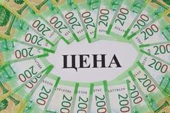 Большая надпись в русской ЦЕНЕ, вокруг новые русские 200 счетов стоковые фото