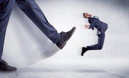 Большая нога пиная малый человека Стоковое Фото