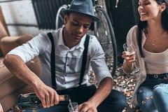 большая партия Взгляд сверху современного whil шампанского молодого человека лить стоковое изображение