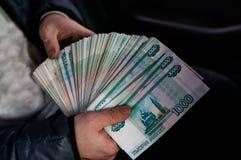 Большая пачка русских денег сжимана в его руке стоковые фотографии rf
