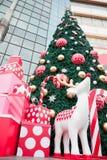 Большая рождественская елка, подарочная коробка и белый цвет северного оленя аранжируют украшенный с красивыми объектами Стоковые Изображения