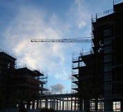 Большая современная строительная площадка в silloute при леса и перила покрывая структуру с краном на заднем плане Стоковые Изображения RF