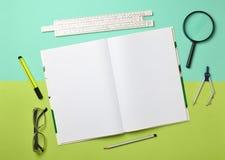 Большая тетрадь для примечаний и чертить с канцелярскими принадлежностями возражает для студента на зеленой голубой пастельной пр стоковое фото