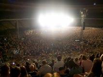 Большая толпа вентиляторов сидя на трибунах стадиона и слушая к концерту рок-музыки вечером Яркие свет и лазер стоковые изображения