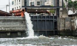 Большая труба водопровода discharging жидкие отходы в реку стоковые изображения rf