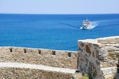 Большая шлюпка плавает на голубом море около каменных стен Стоковое фото RF