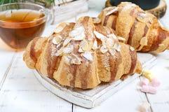 Большие вкусные круассаны с хлопьями миндалины и чашка чаю на белой деревянной предпосылке Стоковое Изображение