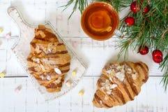 Большие вкусные круассаны с хлопьями миндалины и чашка чаю на белой деревянной предпосылке Стоковые Изображения