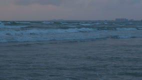 Большие волны пены шторма в море на заходе солнца в темном вечере в темноте Прибрежный город на предпосылке сток-видео