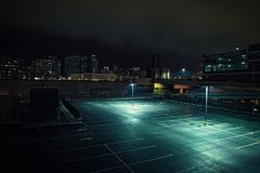 Большие дезертированные городские место для стоянки и гараж города на ноче Стоковые Изображения