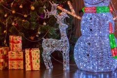 Большие диаграммы ` s Нового Года снеговика, оленя и подарков от накаляя пестротканых гирлянд на предпосылке украшенное artific Стоковая Фотография