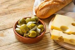 Большие испанские зеленые оливки Gordal с травами и луками в сыре Maasdam багета шара агашка на разделочной доске Стоковые Фото
