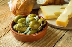 Большие испанские зеленые оливки Gordal с травами и луками в сыре Maasdam багета агашка отрезанном шаром на разделочной доске Стоковое Изображение RF