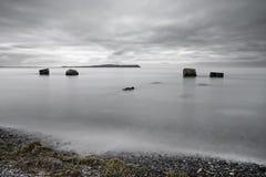 Большие каменные блоки в мелководье перед силуэтом острова стоковое фото
